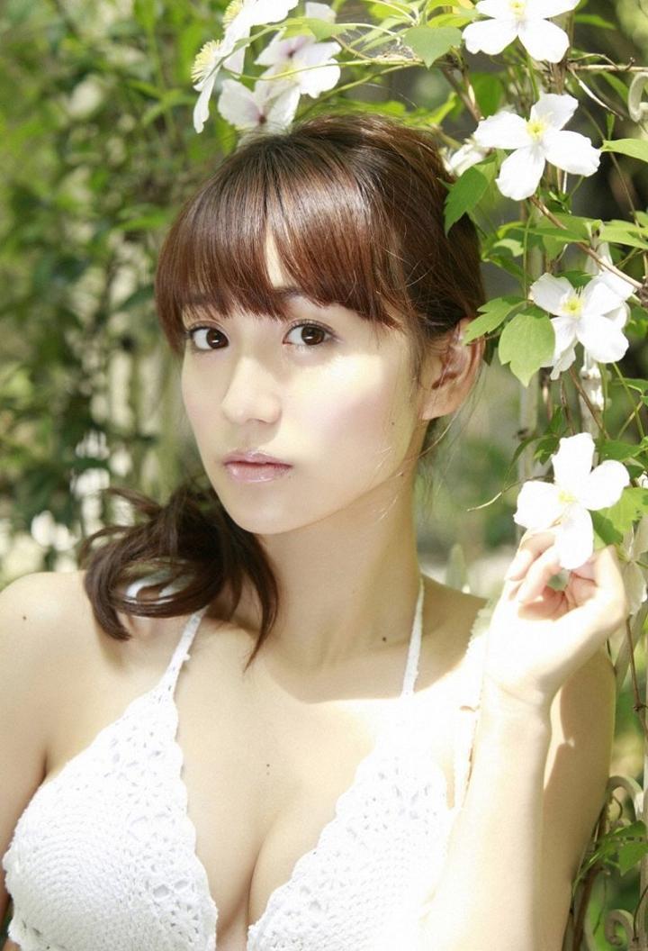 白い花を手に持って同じ色の水着を着てたたずむ大島優子